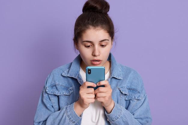 Femmina caucasica che guarda intensamente allo schermo del suo dispositivo con espressione del viso stupita