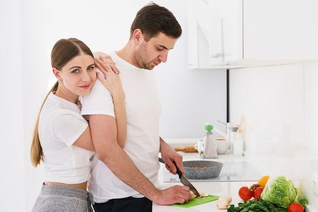 Femmina che abbraccia ragazzo durante la cottura
