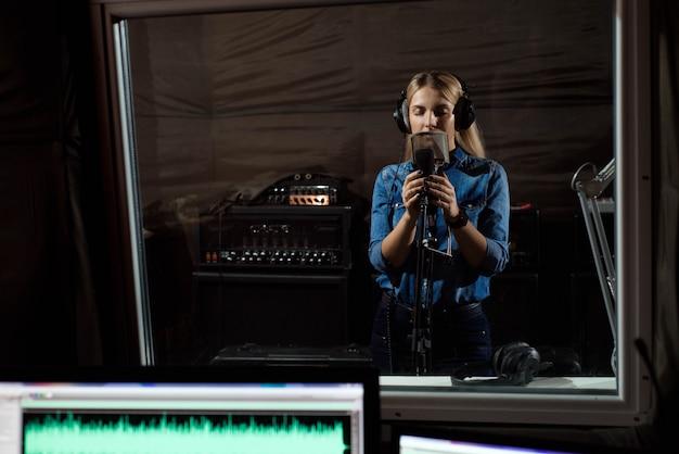 Femmina che canta un canto con il telefono cellulare allo studio di registrazione. voi