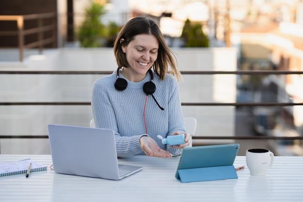 Femmina che lavora da remoto a casa terrazza con laptop e cuffie