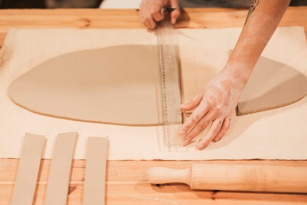 Femmina che misura l'argilla con il righello di plastica sul tavolo