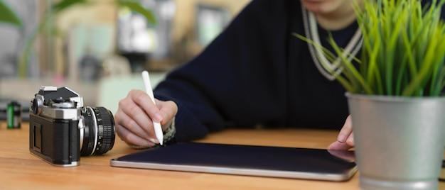 Femmina che per mezzo della compressa digitale sulla tavola di legno con la macchina fotografica e il vaso dell'albero
