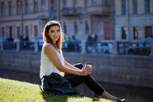 Femmina che si siede sull'erba che beve caffè in una tazza di cartone