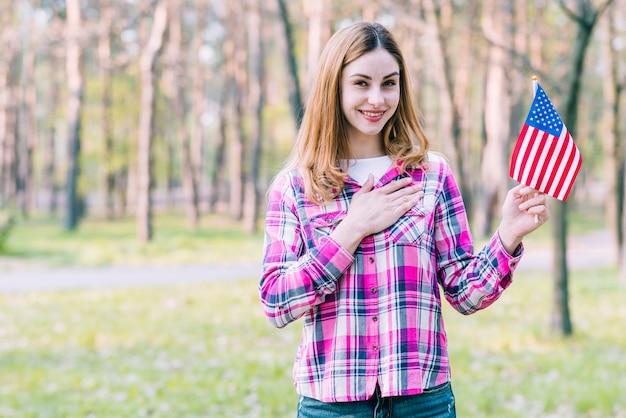 Femmina con bandiera usa in piedi nel parco