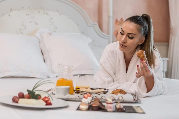 Femmina con cornetto guardando lontano durante la colazione