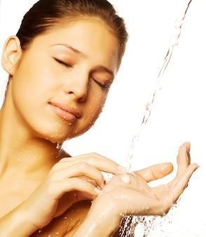 Femmina con gocce d'acqua sul suo viso puro