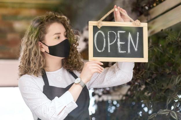 Femmina con maschera tenendo la lavagna con open