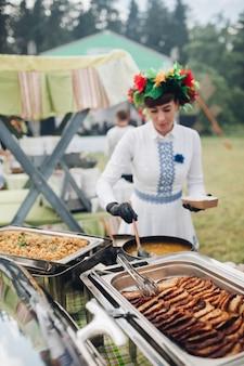 Femmina del cameriere del primo piano che indossa la mano tradizionale del vestito dall'uzbeco che mette pezzo di carne arrostito