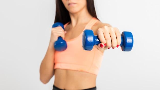 Femmina del primo piano ad addestramento della palestra con i pesi