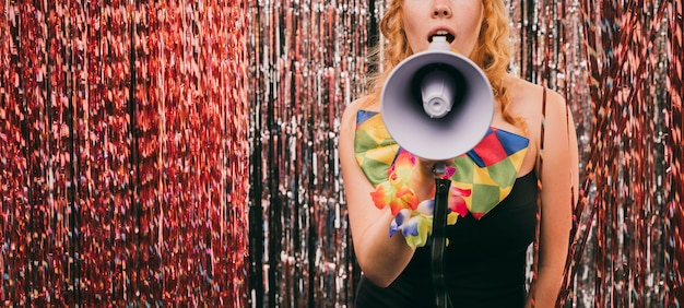 Femmina del primo piano con il megafono alla festa di carnevale