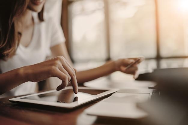 Femmina del primo piano facendo uso della compressa con acquisto online, tono d'annata.