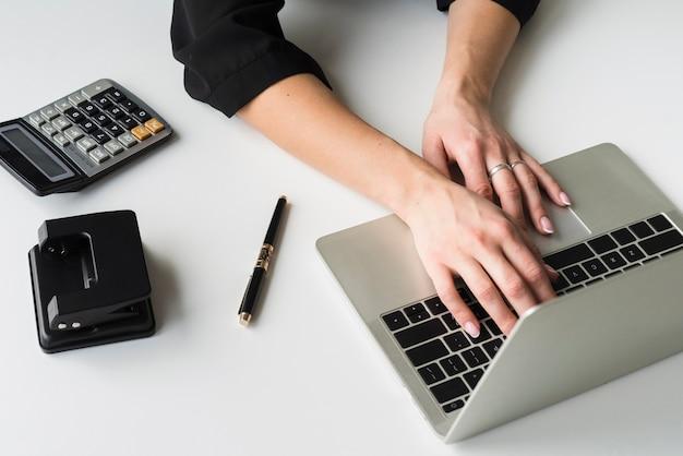 Femmina dell'angolo alto che lavora al computer portatile