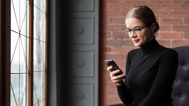 Femmina dell'angolo alto che per mezzo del telefono