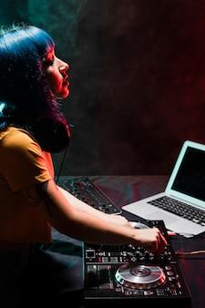 Femmina dell'angolo alto dj nel club che controlla suono