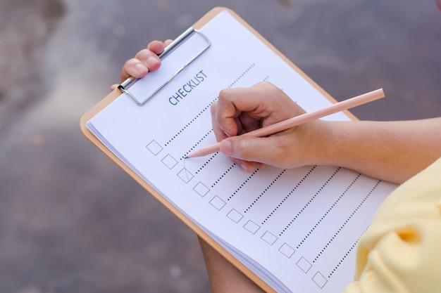 Femmina di affari che prepara lista di controllo alla scrivania