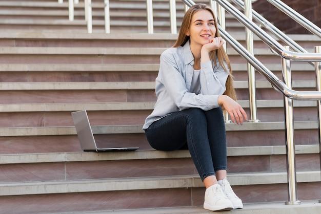 Femmina di angolo basso sulle scale con il computer portatile accanto