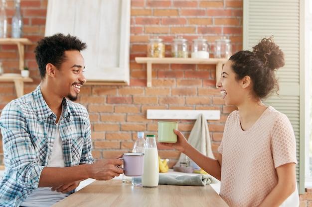 Femmina e maschio allegri allegri in abiti casual bevono latte in cucina, ridono rumorosamente mentre si raccontano storie divertenti.