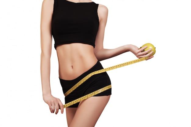 Femmina esile che misura la sua vita sottile con una misura di nastro isolata su bianco.