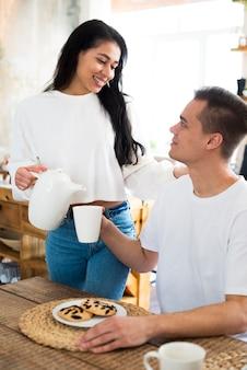 Femmina etnica sorridente che versa in tazza per il ragazzo