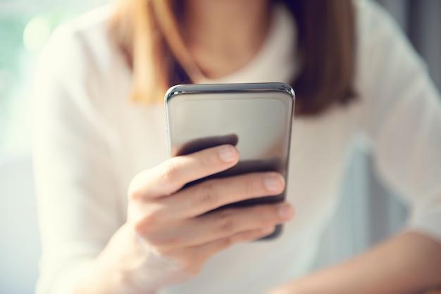 Femmina felice che per mezzo dello smartphone alla caffetteria moderna
