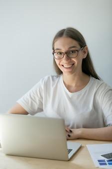 Femmina felice che propone alla scrivania