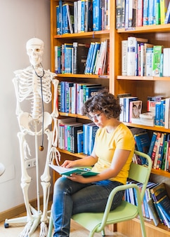 Femmina geek sulla sedia seduta con il libro