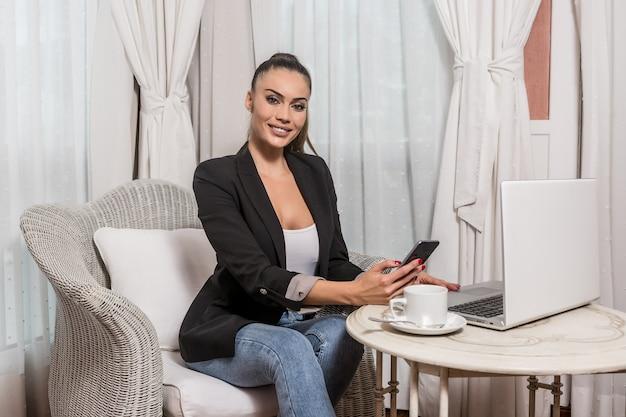 Femmina graziosa con lo smartphone che lavora al computer portatile