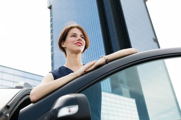 Femmina in abito da ufficio ariives al lavoro in auto e sorrisi