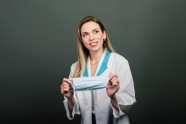 Femmina in abito medico con maschera medica nelle mani.