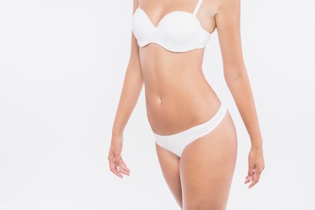 Femmina in biancheria intima bianca che si leva in piedi sulla priorità bassa bianca