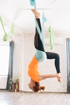 Femmina in buona salute che fa yoga aerea con l'allungamento della gamba