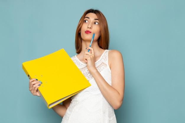 Femmina in camicetta bianca e blue jeans che tengono file gialli