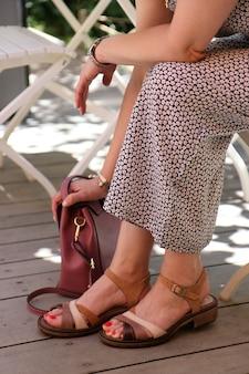 Femmina in un abito seduto con la mano sulla sua borsa