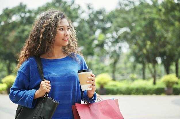 Femmina indonesiana che cammina sulla strada dopo lo shopping