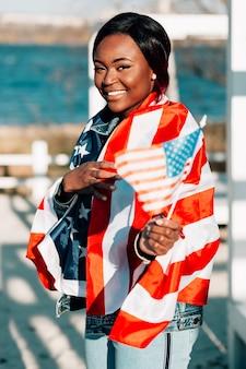 Femmina nera allegra con le bandiere che stanno sulla spiaggia