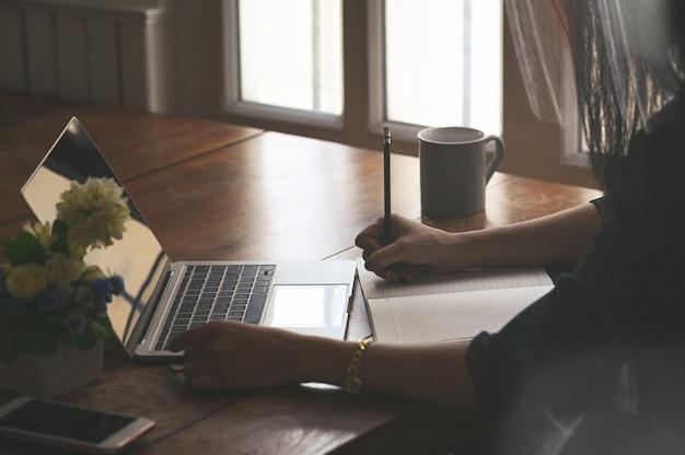 Femmina potata del colpo che per mezzo del computer portatile e bagnando sulla carta per appunti.