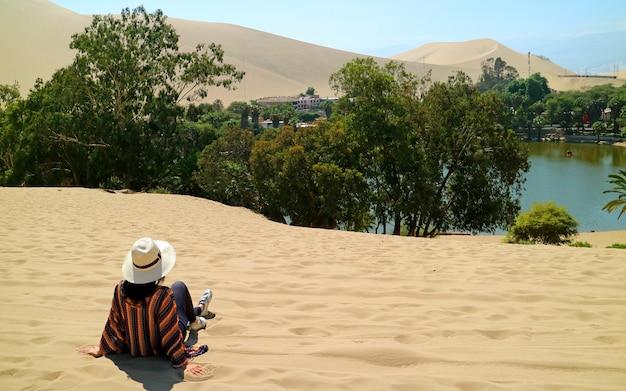 Femmina rilassante sulla duna di sabbia, ammirando la città oasi di huacachina, ica, perù