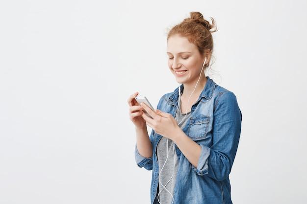 Femmina rossa allegra attraente con panino, ridendo mentre si guarda lo schermo dello smartphone, sms e ascolto musica in cuffia