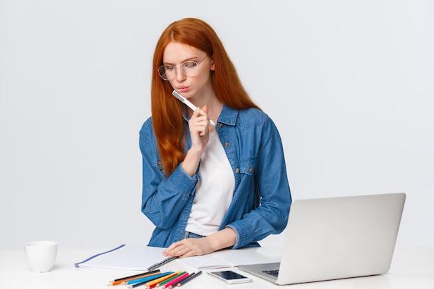 Femmina rossa concentrata e determinata dall'aspetto serio che lavora su un importante progetto, progetta per azienda, lavora come freelance, pensa, medita come scrive, sta vicino al laptop e alle matite colorate