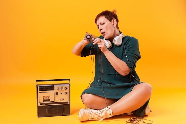 Femmina senior che gioca con il nastro a cassetta