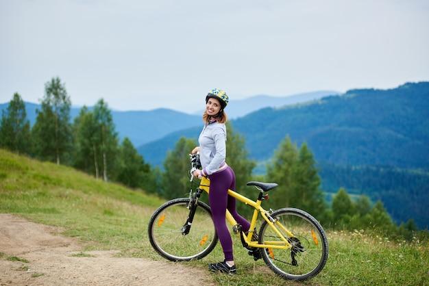 Femmina sorridente attiva con la bicicletta gialla su un sentiero rurale sull'alta catena montuosa, indossando il casco. montagne. attività sportiva all'aperto, concetto di lifestyle