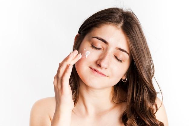 Femmina sorridente che applica crema per il viso