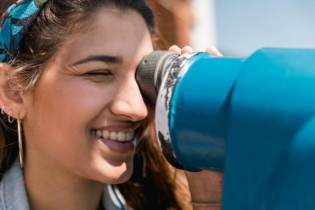 Femmina sorridente che osserva tramite il binocolo