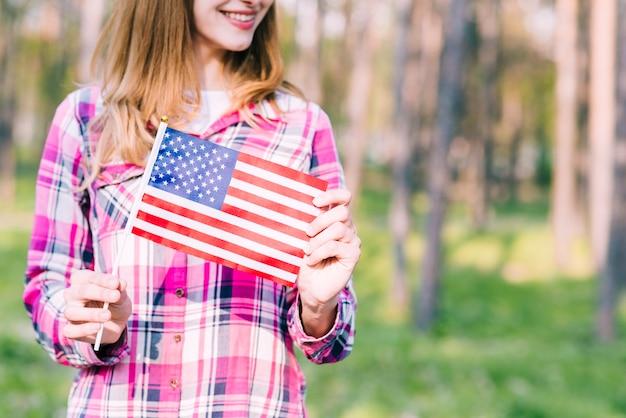 Femmina sorridente con la bandiera americana in mani