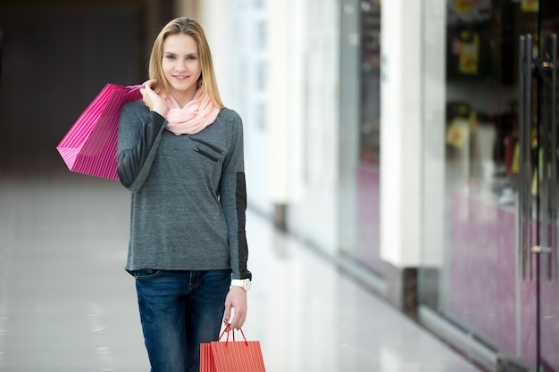 Femmina sorridente nel centro commerciale che cammina con i sacchetti di carta