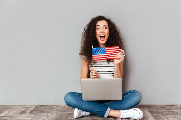 Femmina splendida con il bello sorriso che si siede nella posa del loto con il computer d'argento sulle gambe che dimostrano bandiera americana sopra la parete grigia
