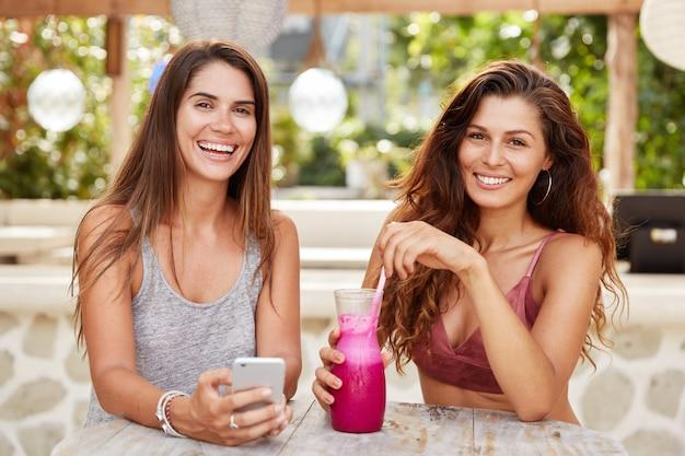 Femmine contente con sguardi felici, divertirsi insieme, leggere commenti nel blog su smartphone, bere bibite fresche, sedersi in una caffetteria all'aperto.