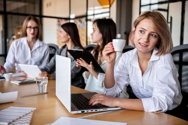 Femmine dell'angolo alto che lavorano e che bevono caffè