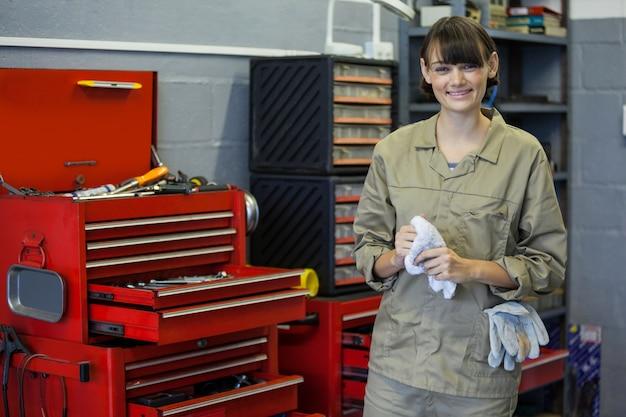 Femminile in piedi accanto meccanico kit di strumenti in un garage di riparazione