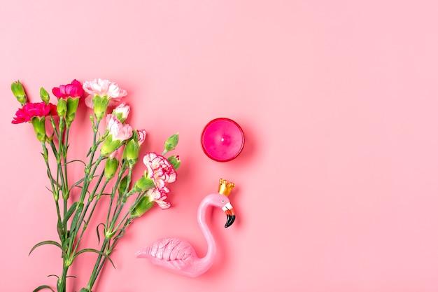 Fenicottero, fiori di garofano, candela su sfondo rosa